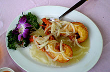 Photo of split lobster claw on plate, covered by onions