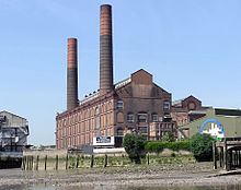 A large red-brick building with a double-pitched roof stretches into the distance. Two cylindrical chimneys reach high into the sky.