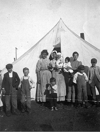 Ludlow Massacre - Three women, wives of striking coal miners, and their children stand outside of a tent at the Ludlow colony.