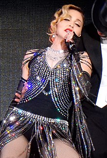 Madonna wearing a gray sparkly outfit, sings to a microphone in her hand.
