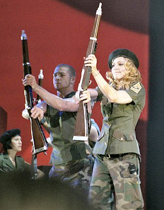 "Express Yourself (Madonna song) - Madonna and her dancers twirling army rifles during a military-themed performance of ""Express Yourself"" on 2004's Re-Invention World Tour."
