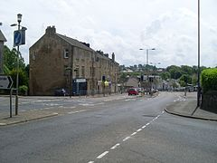 Road junction with view towards three-storey sandstone buildings