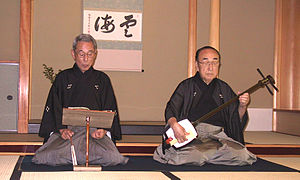 Shamisen - A Japanese man playing a shamisen while another sings