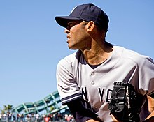 Mariano Rivera in a gray baseball uniform, navy blue cap, and baseball glove bearing his name. He is finishing his throwing motion to the left, and is squinting in the daytime sunny conditions.
