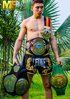Mathias Gallo Cassarino Muay Farang Team Captain holding his Muay Thai Belts (WPMF, WMF, ect).
