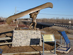 Voyageur statue in Mattice. Bridge over the Missinaibi River is in the background.