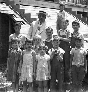 Robert Maestri - Maestri poses with children during a 1938 tour of Works Progress Administration projects around the city