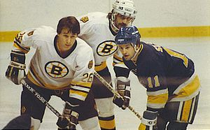 Brian Sutter - Brian Sutter awaiting a face-off with Mike Milbury (pictured left) and Charlie Simmer (pictured center) of the Boston Bruins at the Boston Garden on March 21, 1985 (final score: Bruins 1 – Blues 1/OT).