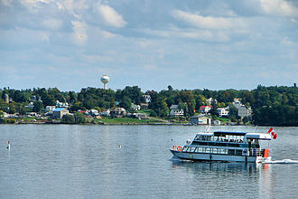 Brockville - Tour boat on the Saint Lawrence River with Morristown visible on the opposite shore. This major river was named by French explorers in the 1700s to commemorate the martyred Christian Lawrence of Rome.