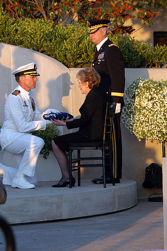 Genuflection - Capt. James A. Symonds, Commanding Officer of the USS Ronald Reagan, presenting the former President's casket flag to former First Lady Nancy Reagan