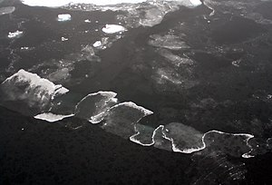 Finger rafting - Aerial photograph showing two thin ice sheets (made of nilas) that are moving toward each other. Along the length of the contact between the two sheets, segments where one sheet climbs onto the other alternate with others where it is the other way around. The lighter areas are where the ice thickness has doubled due to the overlapping process. This pattern is known as finger rafting. In many cases, it is highly systematic.