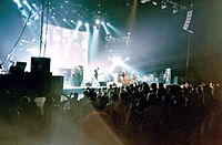 A rock band, Oasis, performing onstage in front of a large projection screen with images on it. Four members are wearing guitars strapped to them.