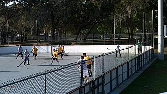 Street hockey - People playing street hockey in an outdoor rink.