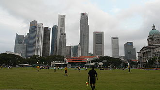 Padang, Singapore - A football match at the Padang set against the Singapore skyline