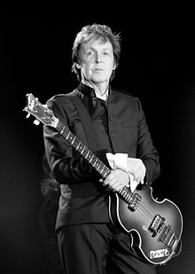 Black and white photograph of McCartney standing onstage holding a bass guitar. He is wearing a dark suit.