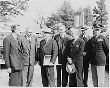 Seven men in suits and one in an Army uniform in a car park.
