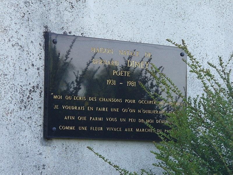 """Sur la plaque: Maison natale de Bernard Dimey Poète 1931 ~ 1981 """"Moi qu'écris des chansons pour occuper mes heures Je voudrais en faire une qu'on n'oublierait jamais Afin que parmi vous un peu de moi demeure  Comme une fleur vivace aux Marches du palais"""""""