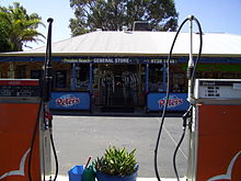 Photo of shop front behind two fuel pumps
