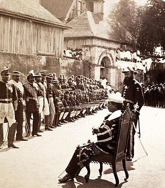 Rainilaiarivony - Wearing a traditional striped lamba over his military uniform, Rainilaiarivony sits to inspect his troops at the Rova compound (around 1865).