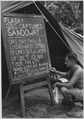 Private First Class Edeleanu prints news bulletin on bulletin board outside Intelligence tent of Kyaukpyu Camp the... - NARA - 540055.tif