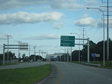 Ground-level view of a four-lane road; a green directional sign is posted above the route, and a traffic signal is visible in the distance.