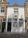 foto van Huis met gepleisterde gevel onder lijst met gevelsteen waarop schip en jaartal