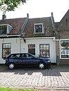 foto van Huisje van alleen parterre met deur en venster, onder hoog zadeldak