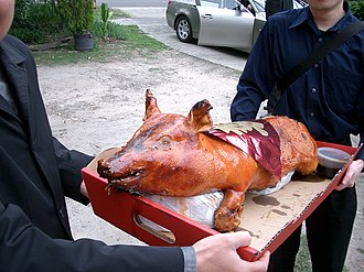 Pig roast - Roast suckling pig bearing 囍 (Double Happiness) placard at a Cantonese wedding