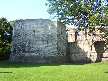 Roman wall and the west corner tower of Eboracum. The top half is medieval. Roman Fortifications in Museum Gardens York.jpg