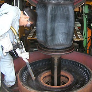 Tire manufacturing - An opened tire mold being cleaned.  The deflated rubber bladder is on the central post.