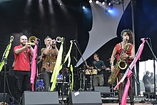 From left to right on a stage: a trombonist, trumpeter, two drummers in the background, and a saxophonist, all playing in bright colors