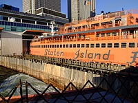 "An orange Staten Island Ferry ship; the words ""Staten Island"" are seen on the side of the ship."