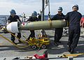 Sailors assigned to the USS Stout transport an M-46 Torpedo. (27060767911).jpg