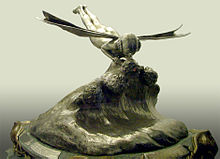 A trophy with a bronze coloured base, above the base is a wave of silver coloured metal. Atop the wave is a silver winged figurine kissing another figurine partly submerged in the wave.