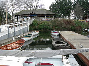 "Center for Wooden Boats - CWB's ""lagoon"", with a Beetle Cat in the foreground and several wooden rowboats in the background"