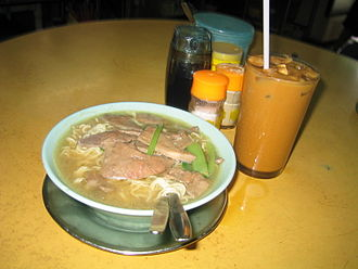 Dai pai dong - Milk tea and a bowl of instant noodle with pig liver, served at a dai pai dong on Yiu Tung Street, Sham Shui Po.