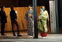 Two young women in kimono stood at a street corner at night. The taller woman wears a casual blue and yellow kimono; the smaller woman is dressed as an apprentice geisha, in a green kimono with green hair accessories and a red underkimono.