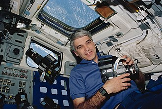 Sidney M. Gutierrez - Astronaut Sidney M. Gutierrez, mission commander, pauses on the flight deck during Earth observations on the Space Shuttle Endeavour. Gutierrez, who was joined by five other NASA astronauts for 11-days in Earth orbit, holds a 70mm Hasselblad camera.