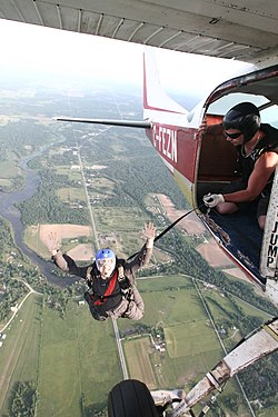 Skydiver exiting aircraft with static line still attached.jpg