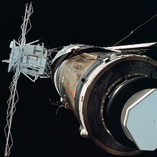 An image of Skylab. The left side of the frame is dominated by a communications array, painted white with a cylindrical satellite dish on top. On they right is a brown-grey cylinder, which is the main station. No solar arrays are visible.