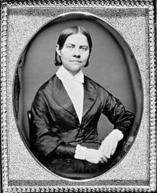 Framed monochrome photograph portrait of a woman sitting, shown from the waist up, left elbow resting on furniture, hands together in lap, the woman wearing a black silk jacket which narrows to conform to the waist, bearing curved lapels, over a plain white blouse with a collar closed at the throat. The woman has dark, straight hair parted in the middle and cut short at the top of the collar. Her head is tilted slightly to her left, face forward, and she is looking directly the observer.