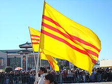 Parade marchers with South Vietnamese flags: three horizontal red stripes on a gold background