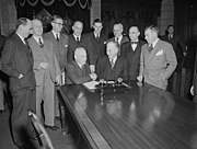 Newfoundland and Canadian Government delegation signing the agreement admitting Newfoundland to confederation in December 1948. Prime Minister Louis St. Laurent and Albert Walsh shake hands following signing of agreement.
