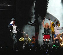 Madonna dancing wearing a red shorts and black, sleeveless top. She is flanked by a man wearing a black pant and jacket, with black hat on his head