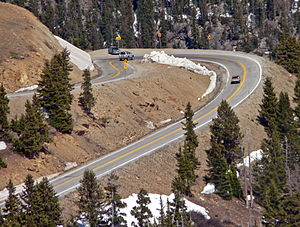=A sharply curved section of road, viewed from above, in a steeply sloped area with large evergreen trees