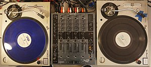 Technics SL-1200 - Two SL-1200s set up for DJ audio mixing. A DJ mixer is placed between the two turntables.