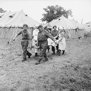 Combat service support - Operation Overlord: Members of the Royal Army Medical Corps carry a wounded soldier out an operating tent on 20 June 1944.