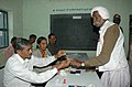 The Electoral Officer applying indelible ink on a old man voter at a polling booth in Gujarat Assembly Election-2007, in Saurashtra on December 11, 2007.jpg