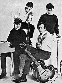 Four young white men posing with electric instruments