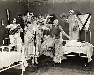 "Wisconsin Center for Film and Theater Research - Scene still from a Mack Sennett Comedy, probably ""Those Athletic Girls"" of 1918. Louise Fazenda does a Russian dance and left of her is Phyllis Haver holding a curling iron. WCFTR Film Title Collection."